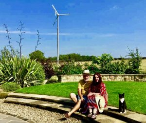 Terry, Tracy and their cat sitting in a garden with a wind turbine visible behind them