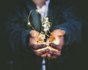 mans hands holding a lightbulb full of small lights