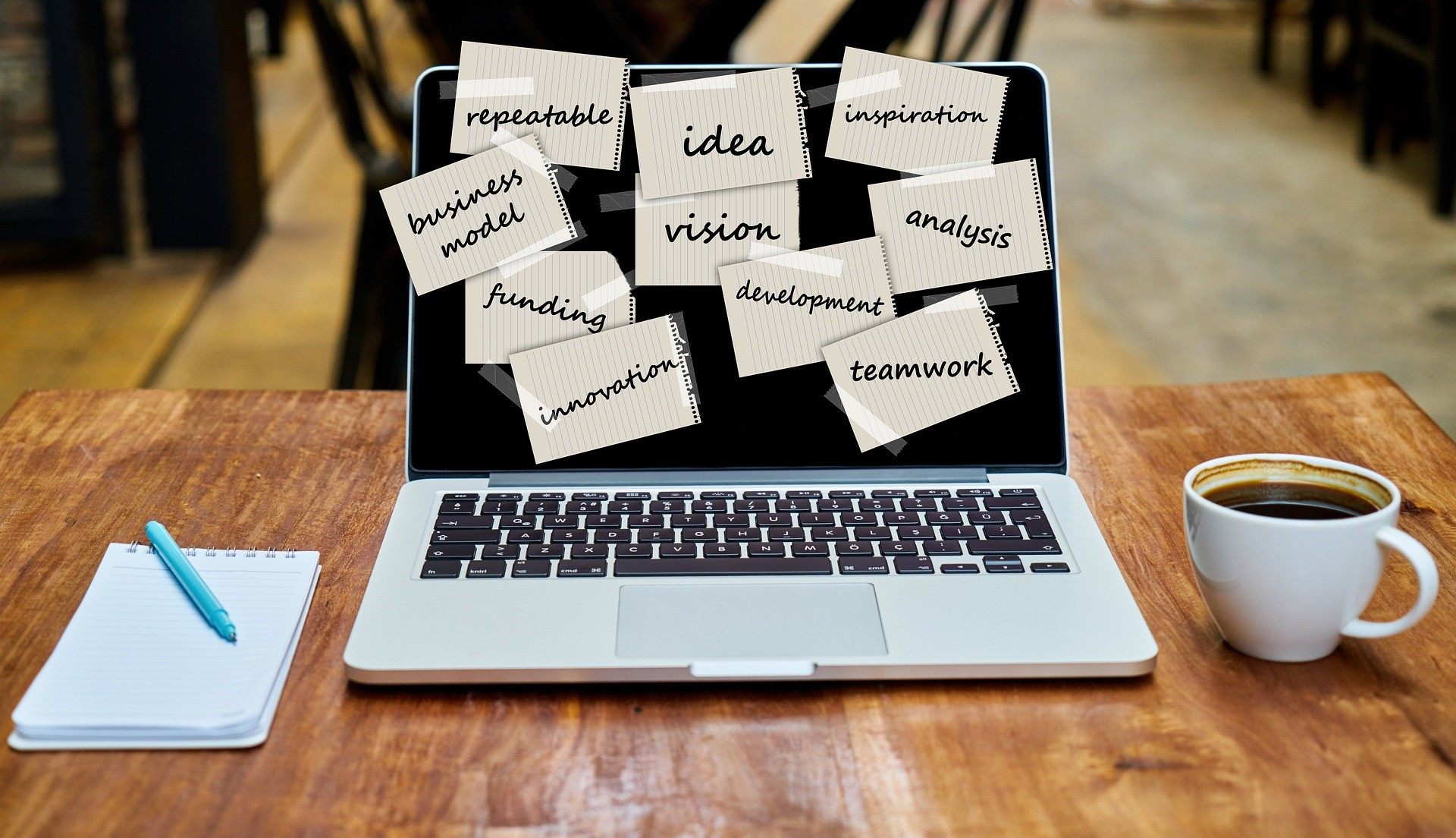 stock photo of a laptop with business buzz words such as idea vision development and teamwork stuck to it