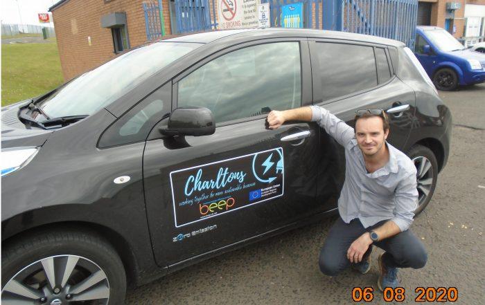 man next to electric vehicle