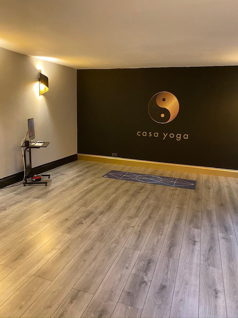Casa Yoga studio room with a large ying yang logo on a dark wall